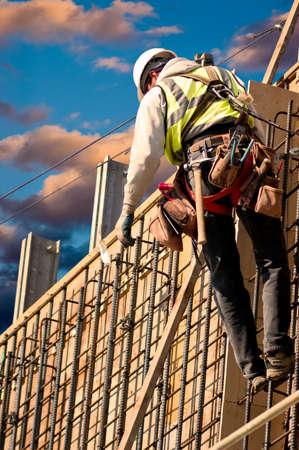 Een bouwvakker op een hoge muur tegen kleurrijke zonsopgang wolken.