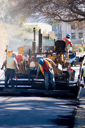 machinery: Men on an asphalt paver repairing a road. Stock Photo