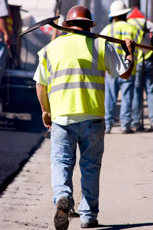 A tired paving worker walking down the street, carrying  a shovel.