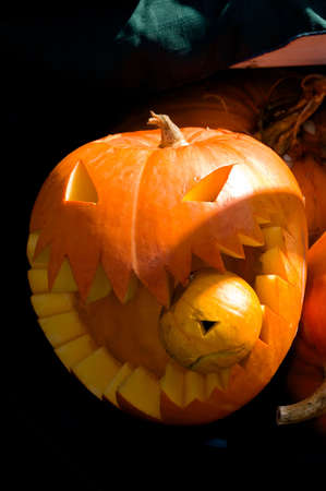 A jack-o-lantern with a smaller jack-o-lantern in its mouth photo