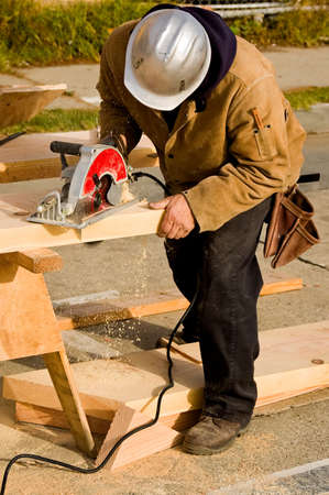 A construction worker cutting a piece of lumber with a circular saw to make a stair stringer Imagens