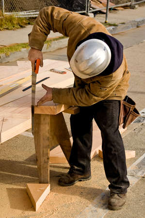 Carpenter using a handsaw to complete a cut Stock Photo - 2369156