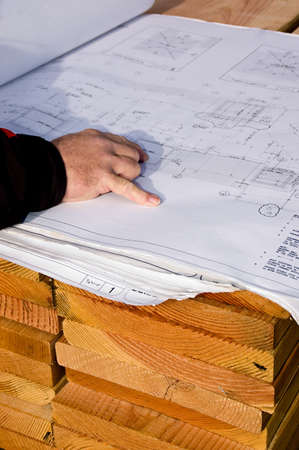 An architect at the job site, checking the project plan