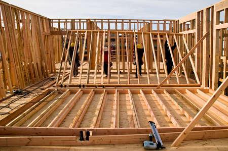 Four workmen raising a new stud wall.