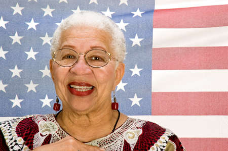 A proud black American woman standing in front of the Stars and Stripes with her hand over her heart.