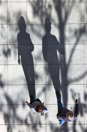 shadow: Two people walking down the street in the late afternoon. Stock Photo