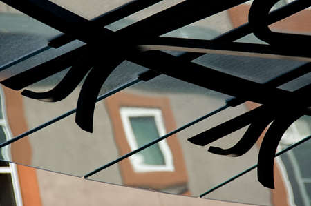 An urban architectural abstraction, iron scrollwork, glass awning and a painted window