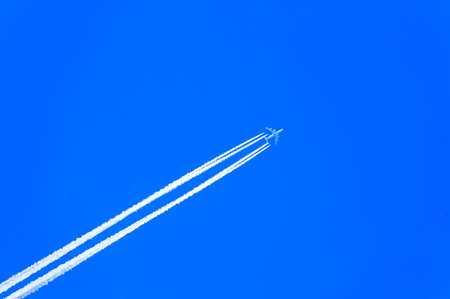A passenger jet at crusing altitude, photographed against a clear blue sky