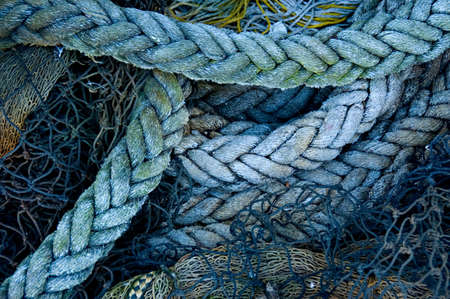A fishermans ropes and nets, piled on a wharf Stock Photo