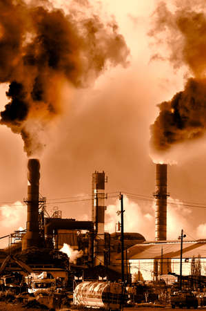 Menacing fumes arising from the smokestacks of an industrial plant Stock Photo