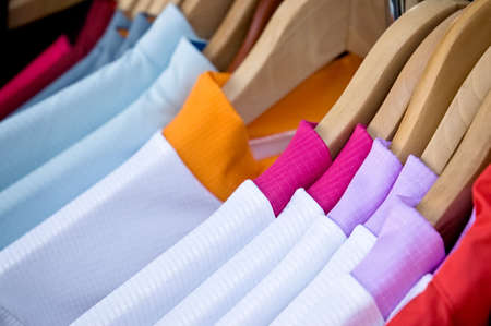 hangers: Shirts with brightly colored collars hanging on wooden clothes hangers