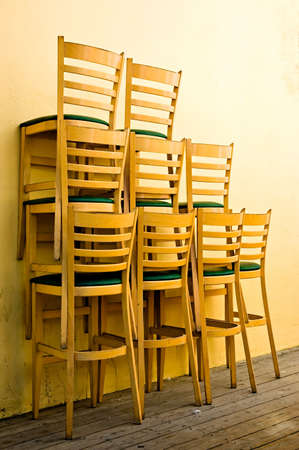 Tall chairs from a restaurant, stacked outside early in the morning Stock Photo