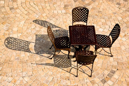 Patio furniture casting strong shadows across a patio tiled in a fan pattern Stock Photo