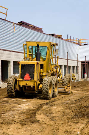 grader: A road grader smoothing the ground around a new building Stock Photo