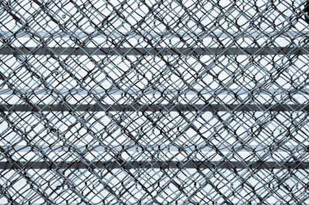 Abstract pattern created on a corrugated metal wall by a chain link fence and shadows. photo