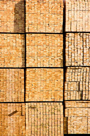 studs: A large stack of new wooden studs at a lumberyard
