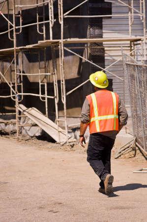Een veiligheidsbeambte stagiair lopen via een baan site Stockfoto