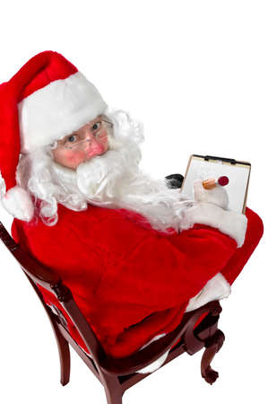 Santa Claus making his list of the good children Stock Photo