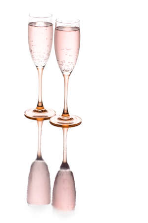 Two champagne glasses sitting on a reflective surface