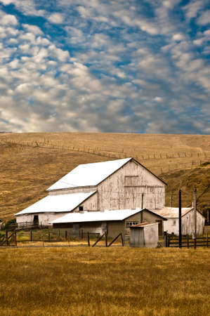 A white barn on a grassy hillside against a cloudy sky Stock Photo - 4061487
