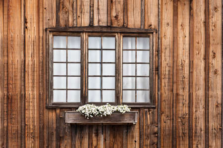 Rustic unpainted cabin window with a flower box Stock Photo