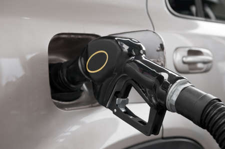 fillup: A gasoline pump nozzle in the tank of an automobile. Stock Photo