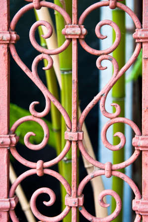 Image of a pink fence with a wrought iron heart, green bamboo in the background Stock Photo
