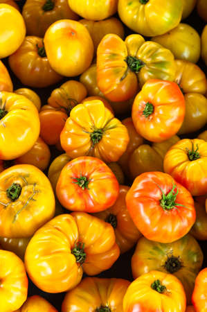 A bunch of yellow organic heirloom tomatoes at a farmers market