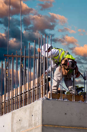 A construction worker guiding a section into place on a high concrete wall at sunrise