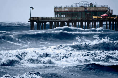squall: Strong storm driven waves pound the wharf