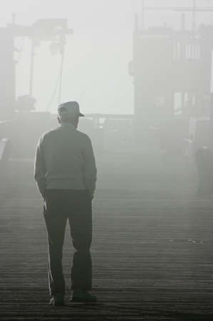 An old man walking into the fog photo