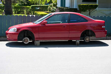 A parked automobile on blocks whose wheels and tires have been stolen photo