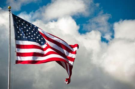 바람이 부는 날에 흐린 하늘을 배경으로 미국 국기 스톡 콘텐츠