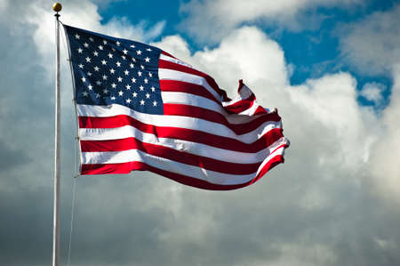 American flag against a cloudy sky on a windy day