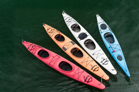 tether: Four colorful fiberglass kayaks on a tether
