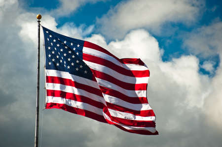 american army: American flag against a cloudy sky on a windy day
