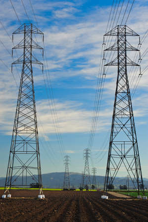 High voltage electrical transmission towers on farmland Stock Photo