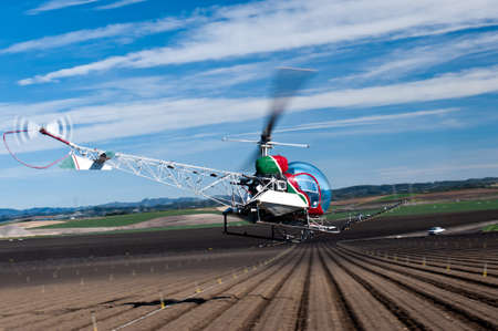 Bell 47 helicopter spraying crops in the Salinas Valley, California Редакционное