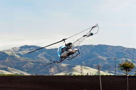 Helicopter spraying agriculture chemicals, making a turn over the field. Stock Photo - 12287544