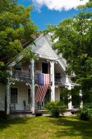 Traditional New Hampshire house draped with an American Flag