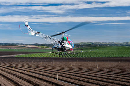 Helicopter spraying pest control chemicals on crops raised conventionally.