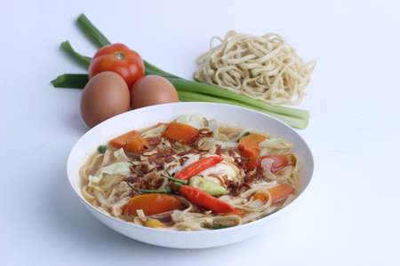 Mie Godog Jawa or Noodle soup is Javanese and Indonesian food with noodle ingredients and cabbage on plate. it tastes delicious. isolated on white background