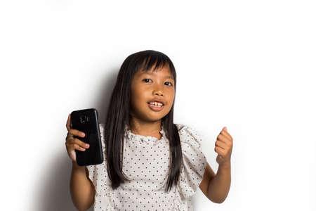 Happy asian little girl using smart phone on white background Stock Photo