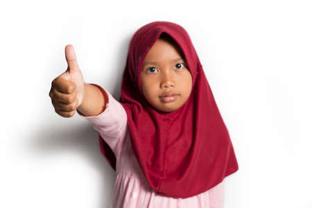 Little asian muslim hijab girl show thumbs up gesture on white background