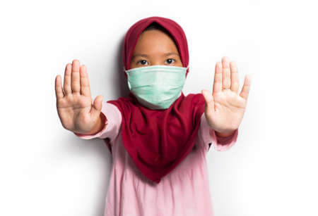 Little asian muslim hijab girl wearing mask show stop hands gesture