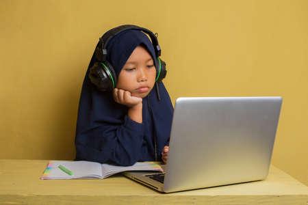 使用她的便携式计算机的聪明的矮小的亚洲穆斯林hijab女孩