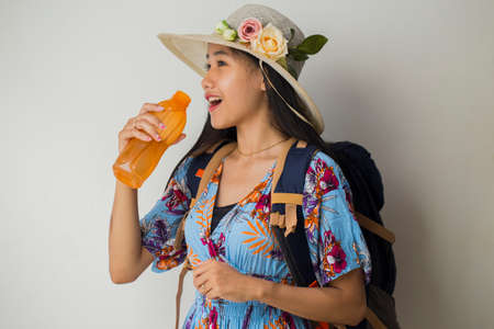 Asian woman tourist with backpack drinking water isolated on white background