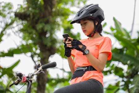 Asian woman cyclist use smartphone when riding bike on city forest.
