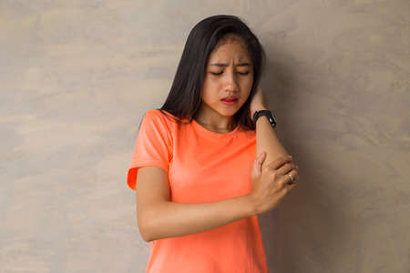 Close up woman having pain in injured elbow.