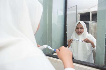 asian muslim woman brush her teeth